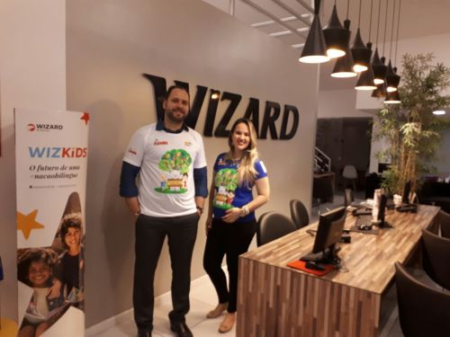 O diretor Cyro Rangel posa ao lado de Clara Gusmao, gerente de uma das unidades Wizard, com a t-shirt da campanha Comece Ajudando em prol da Apala